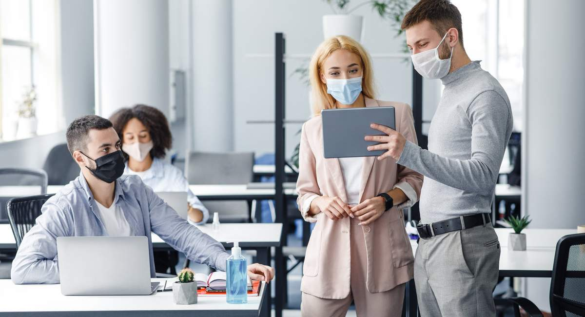 Teamwork in corporate company and social distance during coronavirus epidemic. Male manager in protective mask shows tablet to workers in interior.